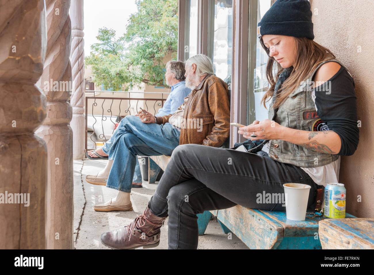 Three people sitting outside a cafe two older men looking away beyond a young woman looking at her mobile phone - Stock Image
