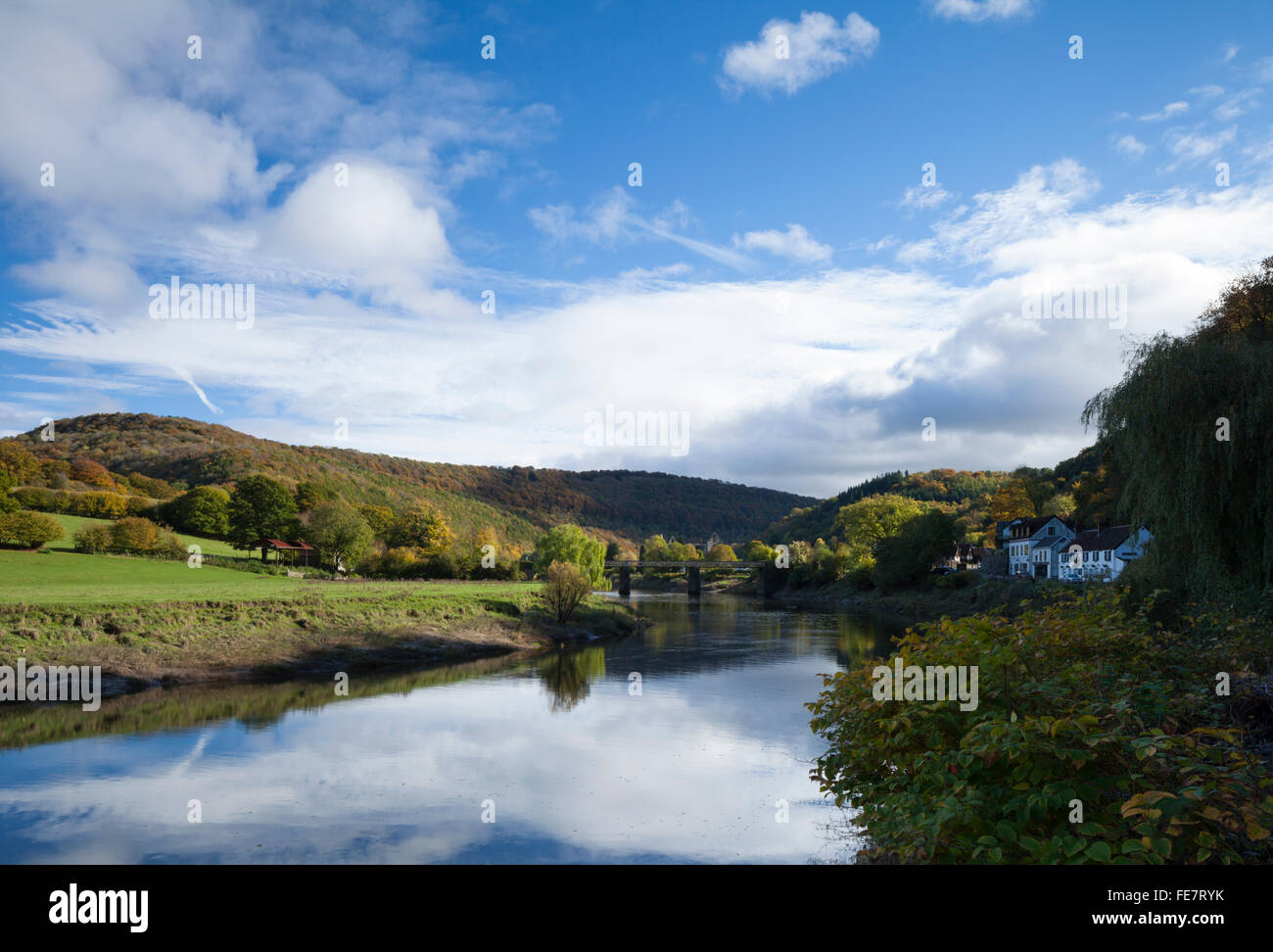 Beside the River Wye at Tintern looking towards the Devils Pulpit and the ruins of Tintern Abbey and old Wireworks - Stock Image