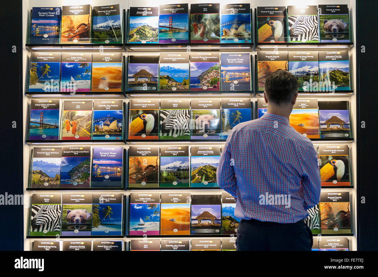 """London, UK.  4 February 2016. A visitor admires travel brochures to exotic places on the opening day of """"Destinations: Stock Photo"""