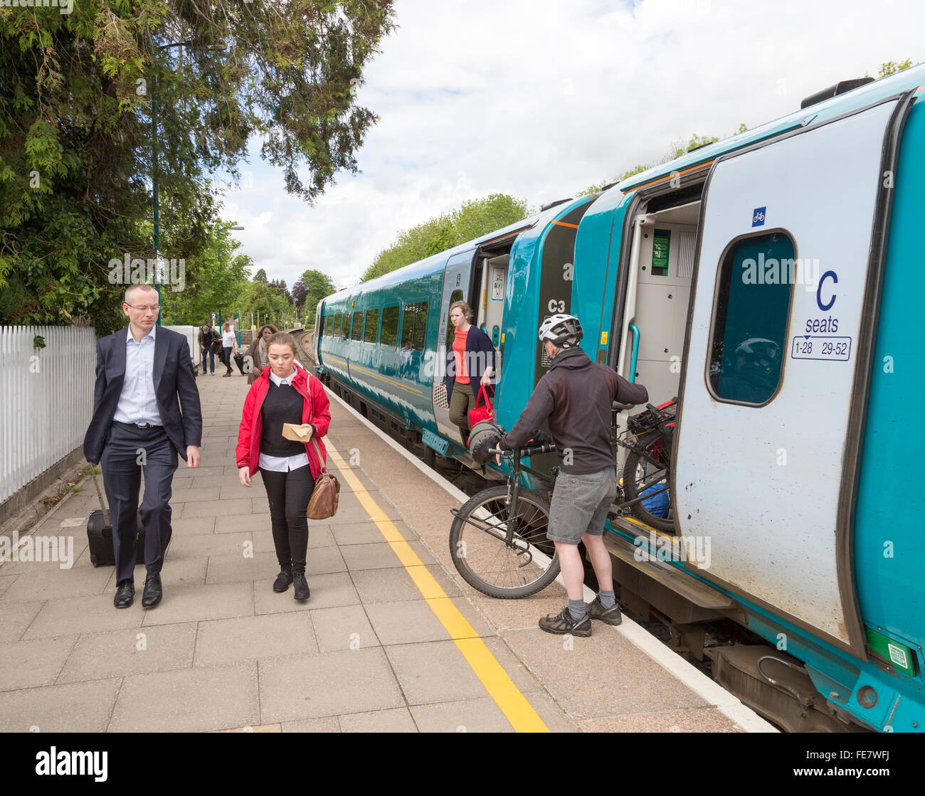 Railway station platform with passengers and bicycle unloading from train, Abergavenny, Wales, UK - Stock Image