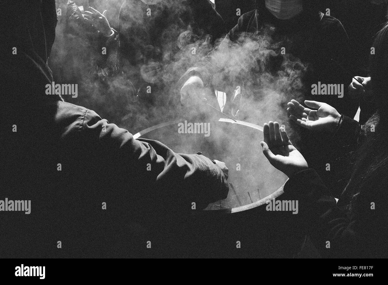 Group Of People Around Smoke Container - Stock Image
