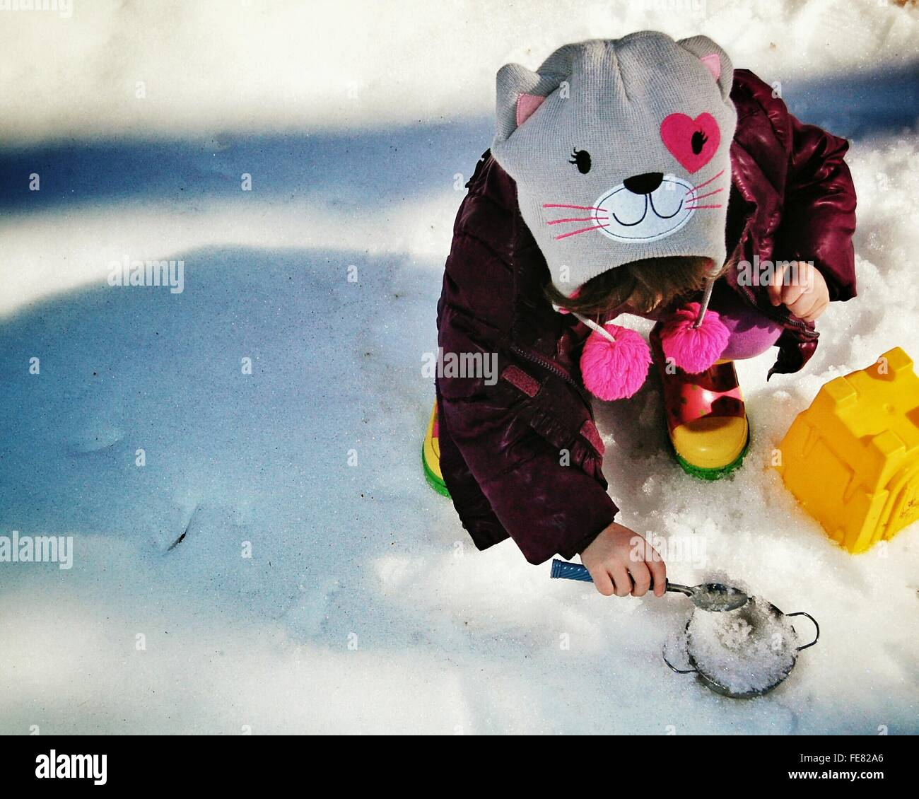 High Angle View Of Little Girl Playing In Snow - Stock Image
