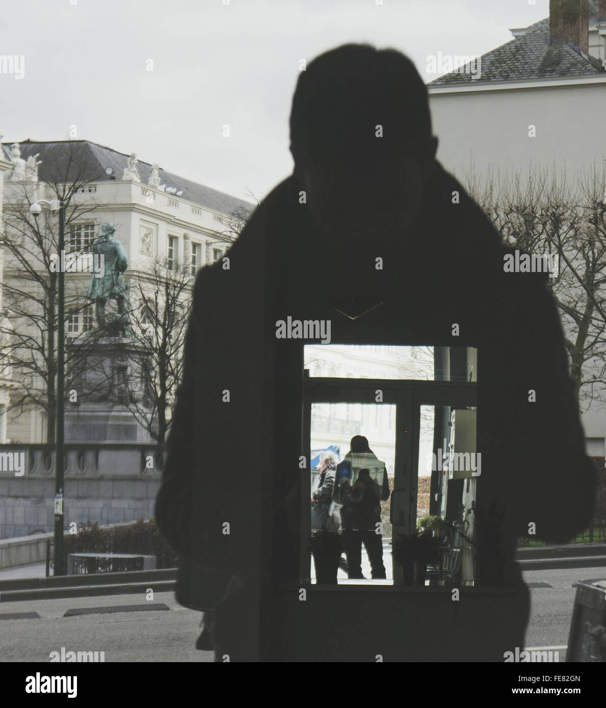 Reflection Of Silhouette Man On Glass Window In City Stock Photo