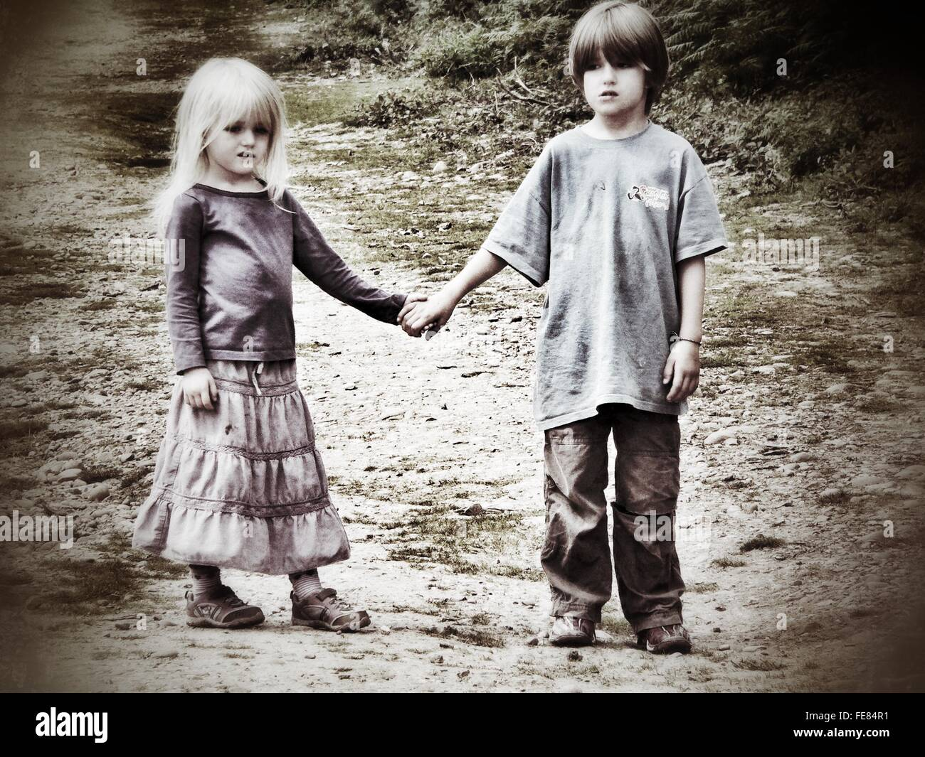 Full Length Of Siblings Holding Hands - Stock Image