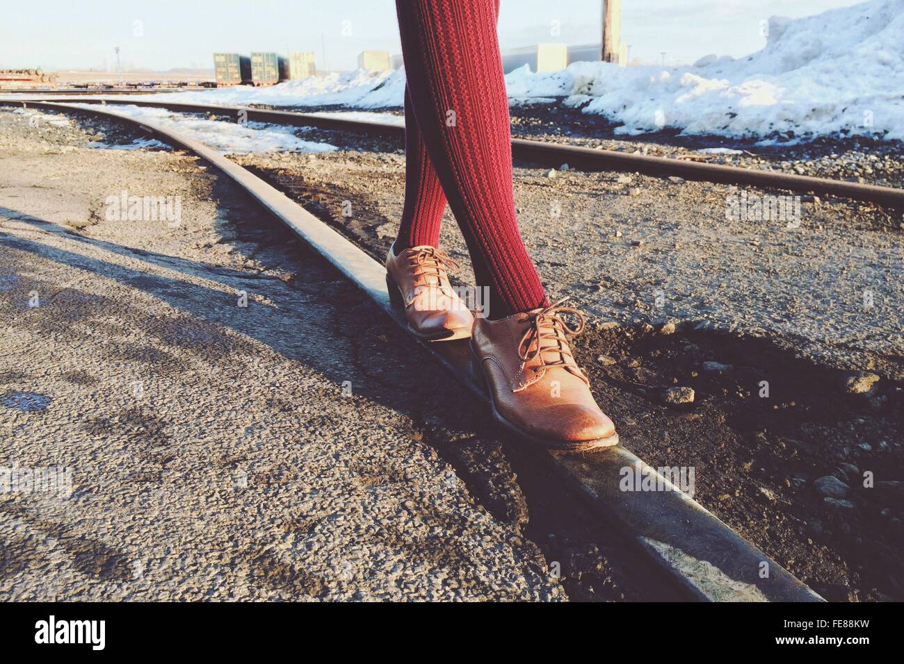 Low Section Of Person Walking On Railroad Track - Stock Image