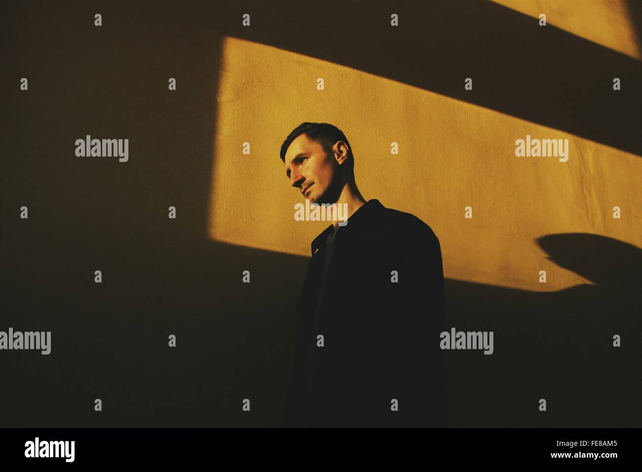 Low Angle View Of Young Man Standing Against Wall - Stock Image