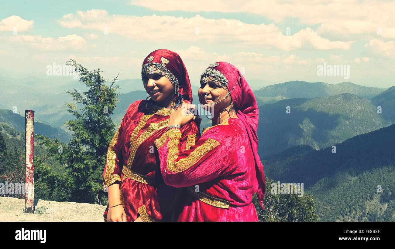 Mother And Daughter In Traditional Clothing Against Mountains - Stock Image