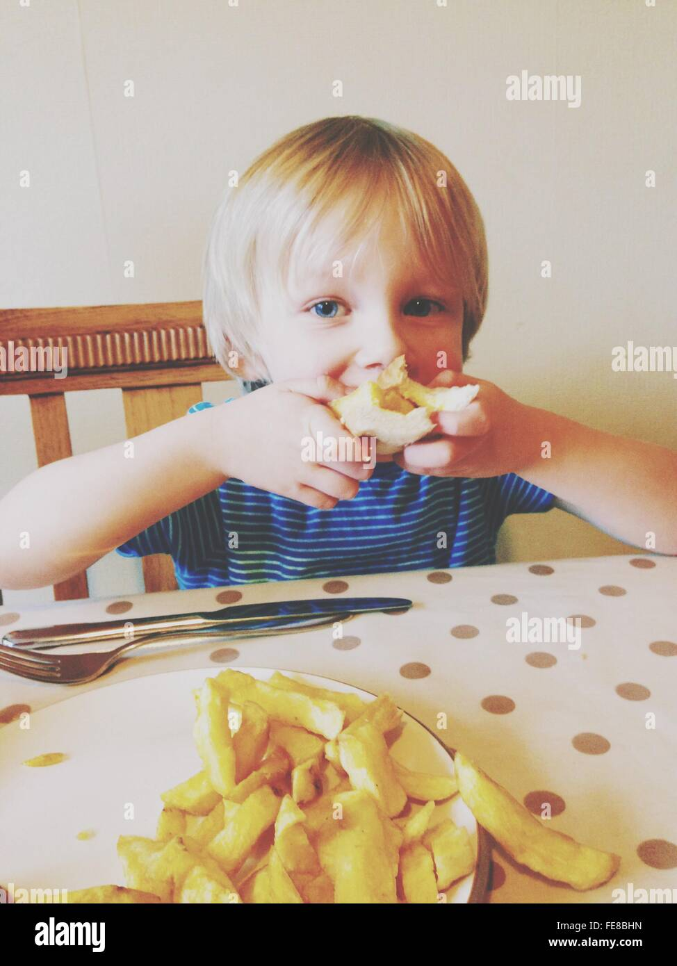 Portrait Of Boy Eating Chip Butty - Stock Image