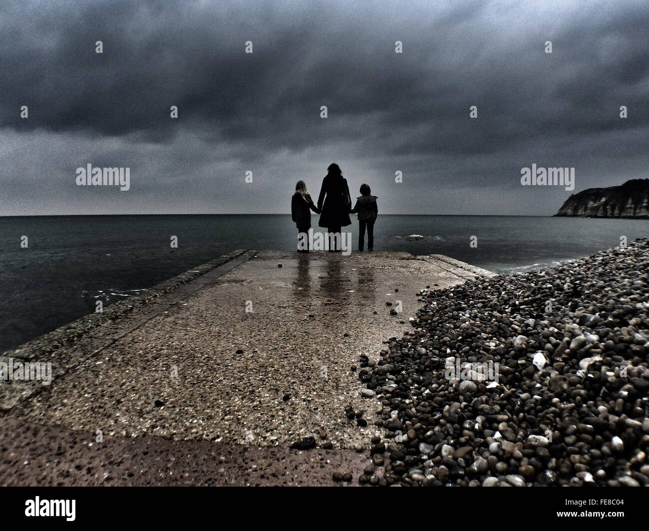Silhouette Of Mother With Children At Beach Coastline - Stock Image