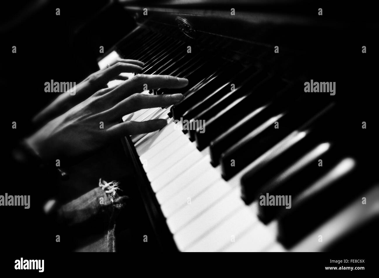 Close-Up Of Person Hands Playing Piano - Stock Image