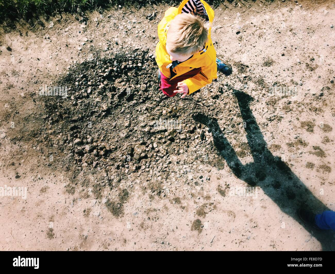 High Angle View Of Boy Jumping On Muddy Puddle - Stock Image