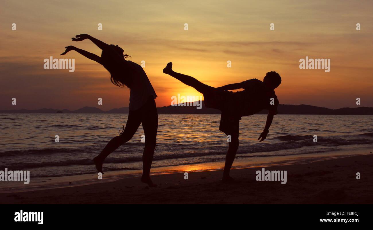 Silhouette Man Hitting Woman On Beach At Sunset - Stock Image