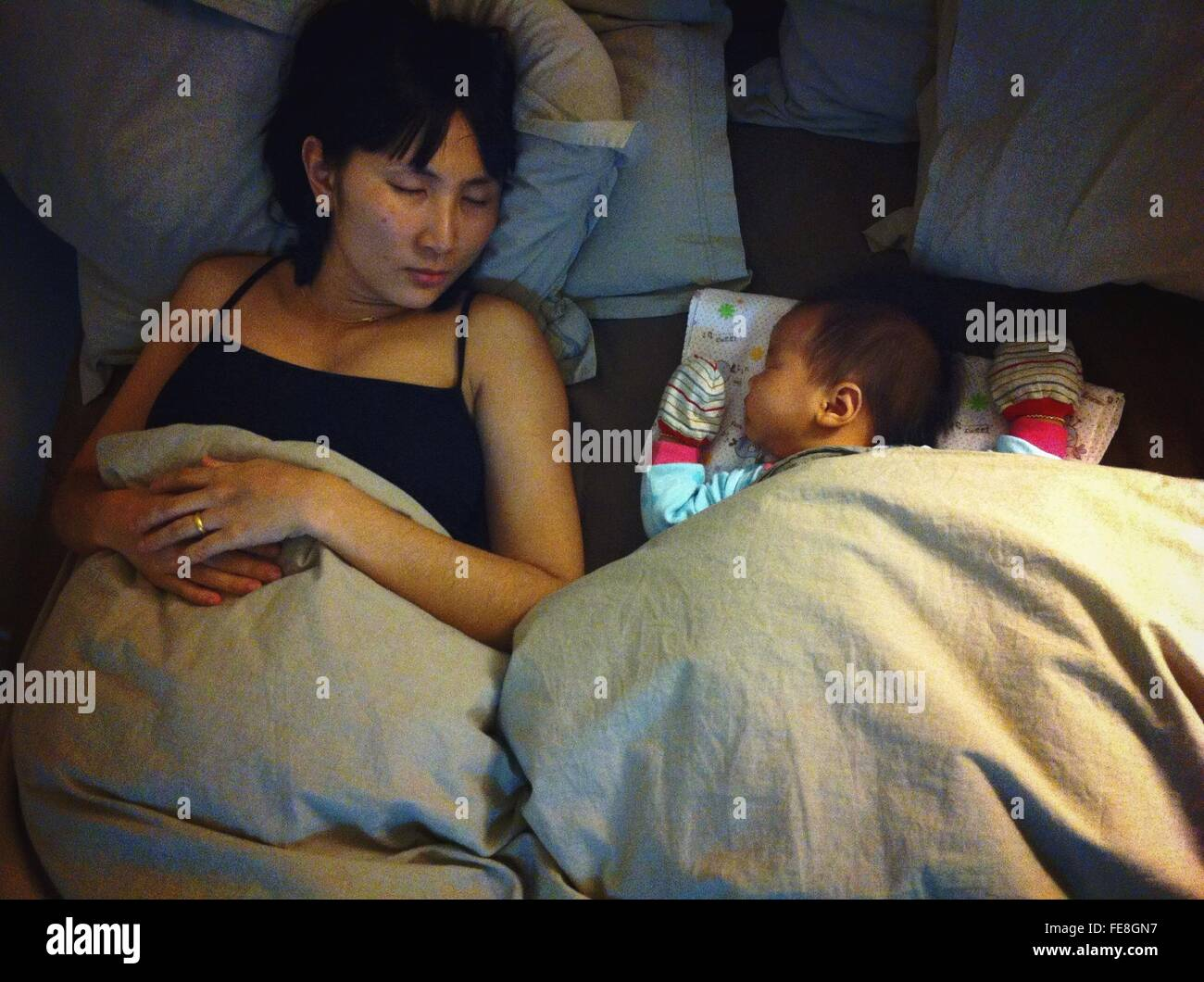 Baby Girl Sleeping With Mother Stock Photo
