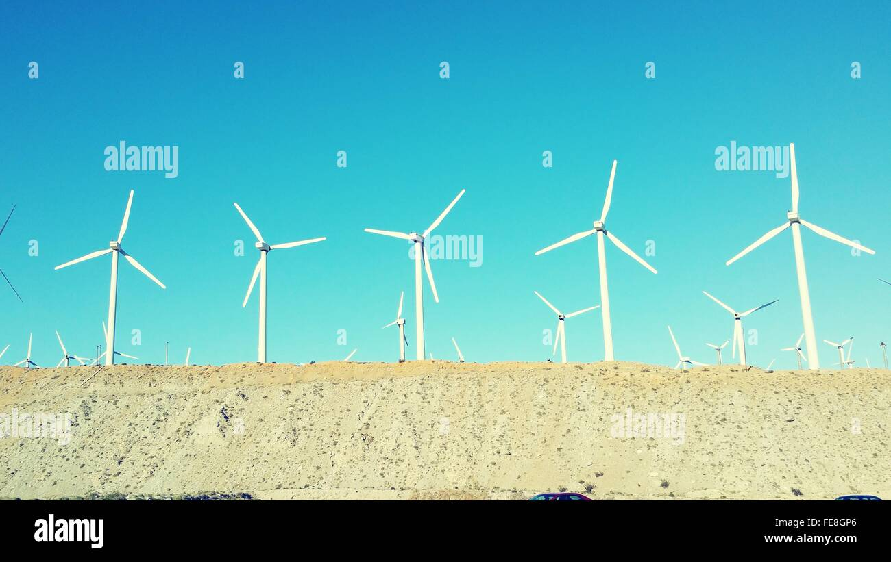 Low Angle View Of Wind Farm Against Clear Sky - Stock Image
