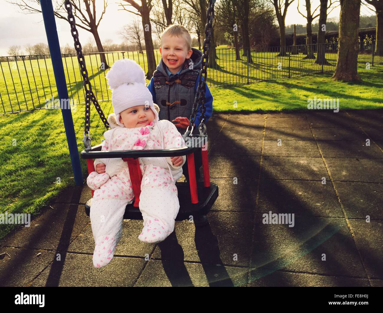 Cute Brother Boy Pushing Sister In Swing At Playground - Stock Image