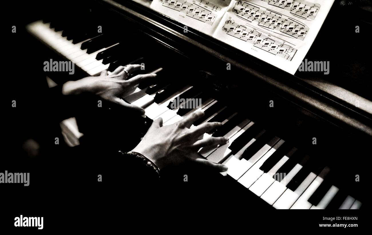 High Angle View Of Cropped Hands Playing Piano - Stock Image