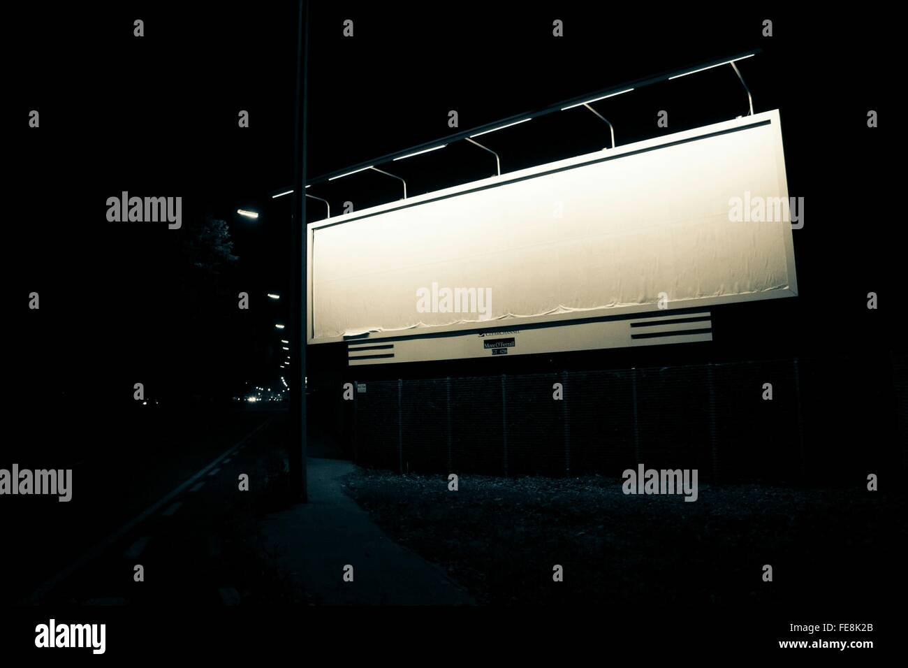 Illuminated Billboard By Street At Night - Stock Image