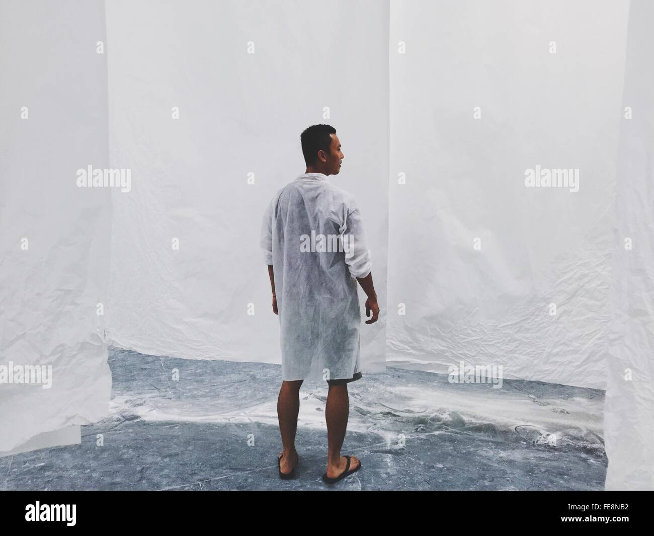 Full Length Rear View Of Man Standing Against White Wall - Stock Image