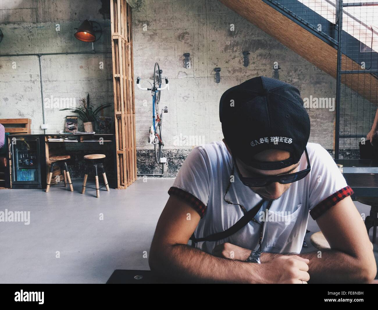 Man In Sunglasses And Cap Looking Down - Stock Image