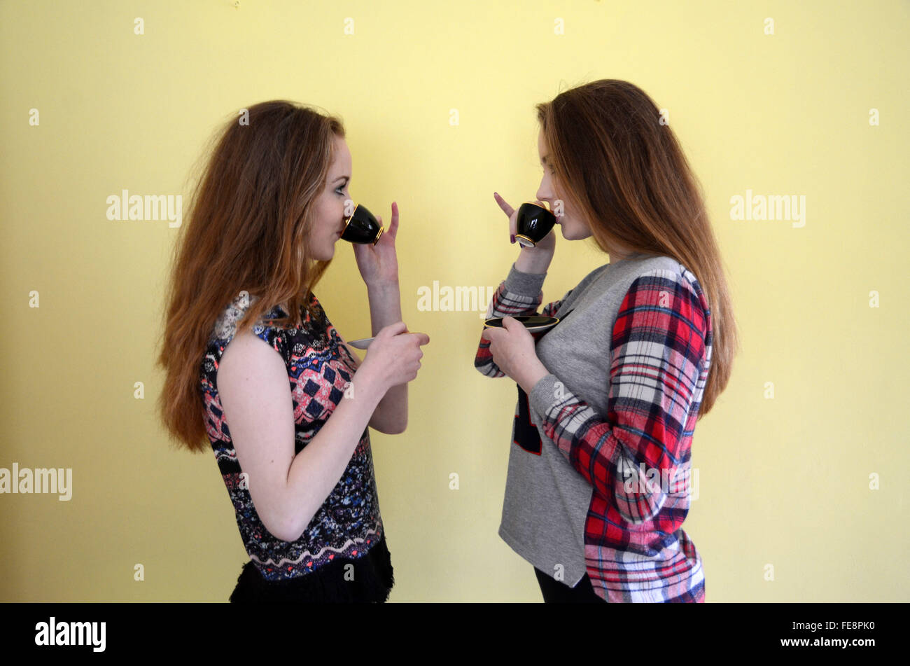 Young Women Drinking Coffee Facing Each Other Against Yellow Wall Stock Photo