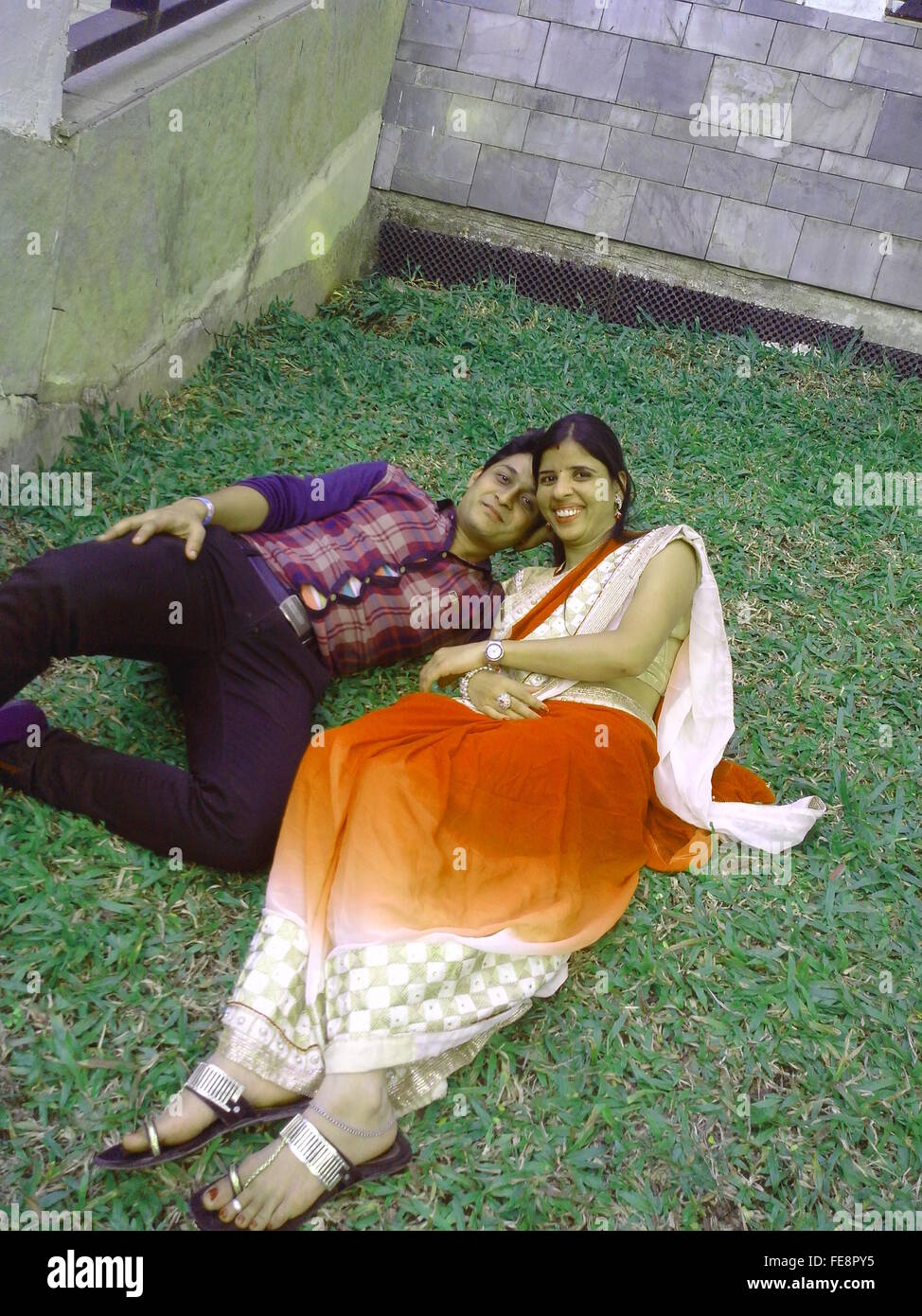 Portrait Of A Young Couple Lying On Grass - Stock Image