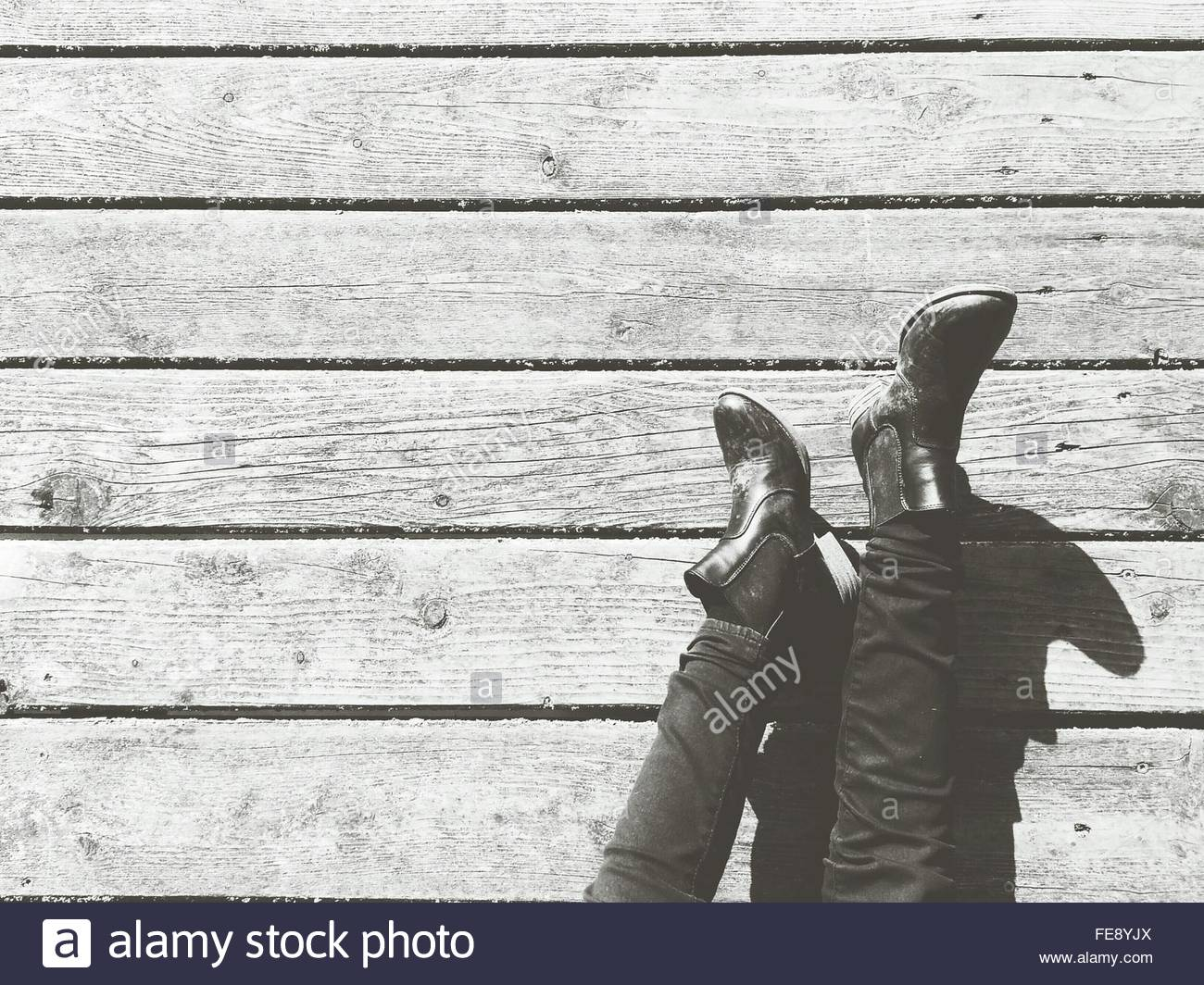 Low Section Of Man Relaxing On Wood Paneled Floor - Stock Image