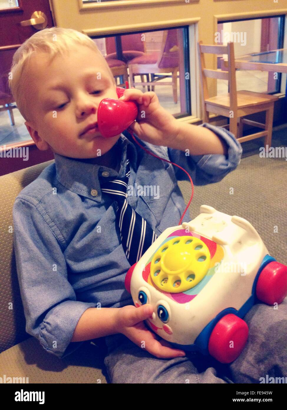 a67efd1ea Boy Playing With Toy Phone While Sitting On Sofa - Stock Image