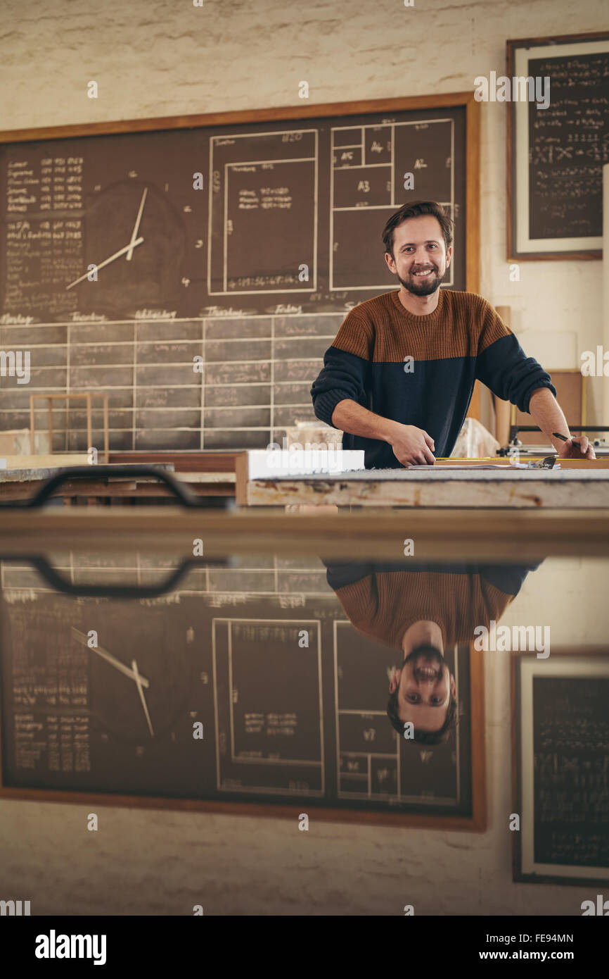 Portrait of a professional craftsman working in his studio on a project Stock Photo