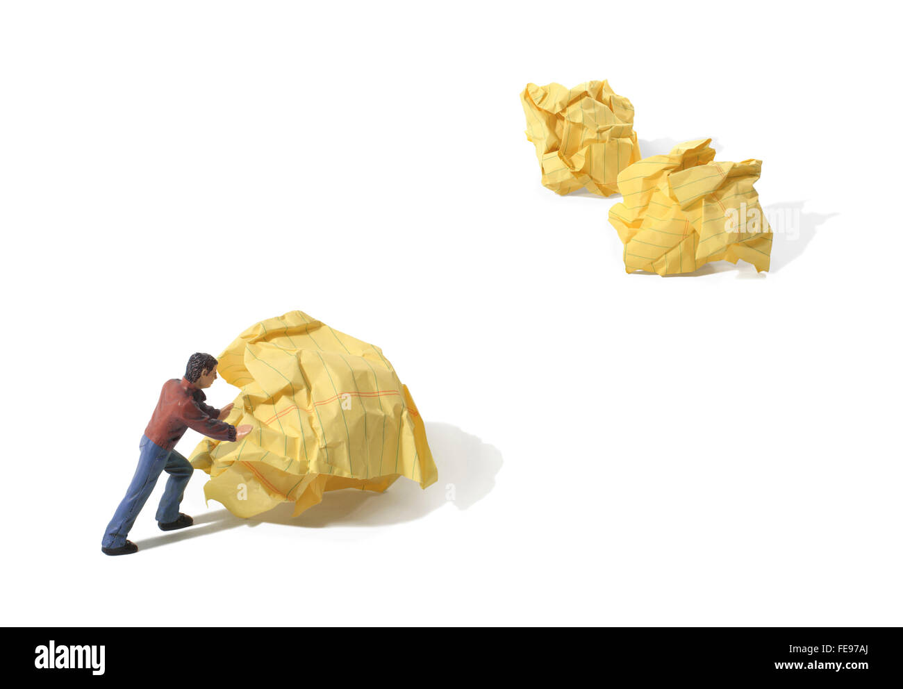 Figure Pushing a Yellow Crumpled Paper Wad on a White Background - Stock Image