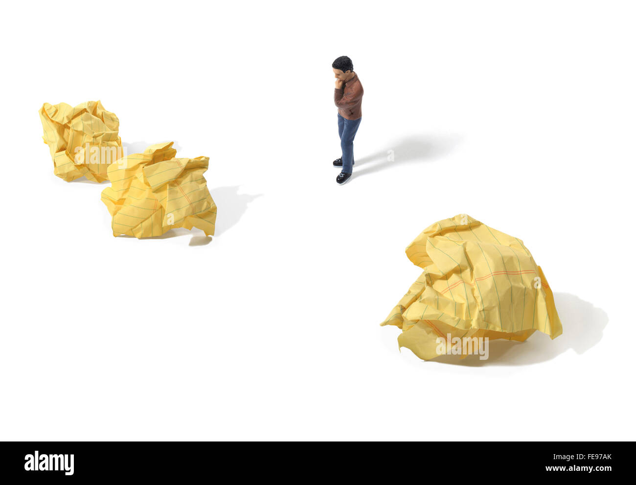 Figure Looking at Crumpled Paper Wads on a White Background - Stock Image