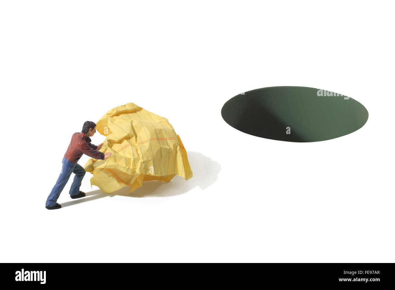Figure Pushing Paper Wad Into a Hole on a White Background - Stock Image