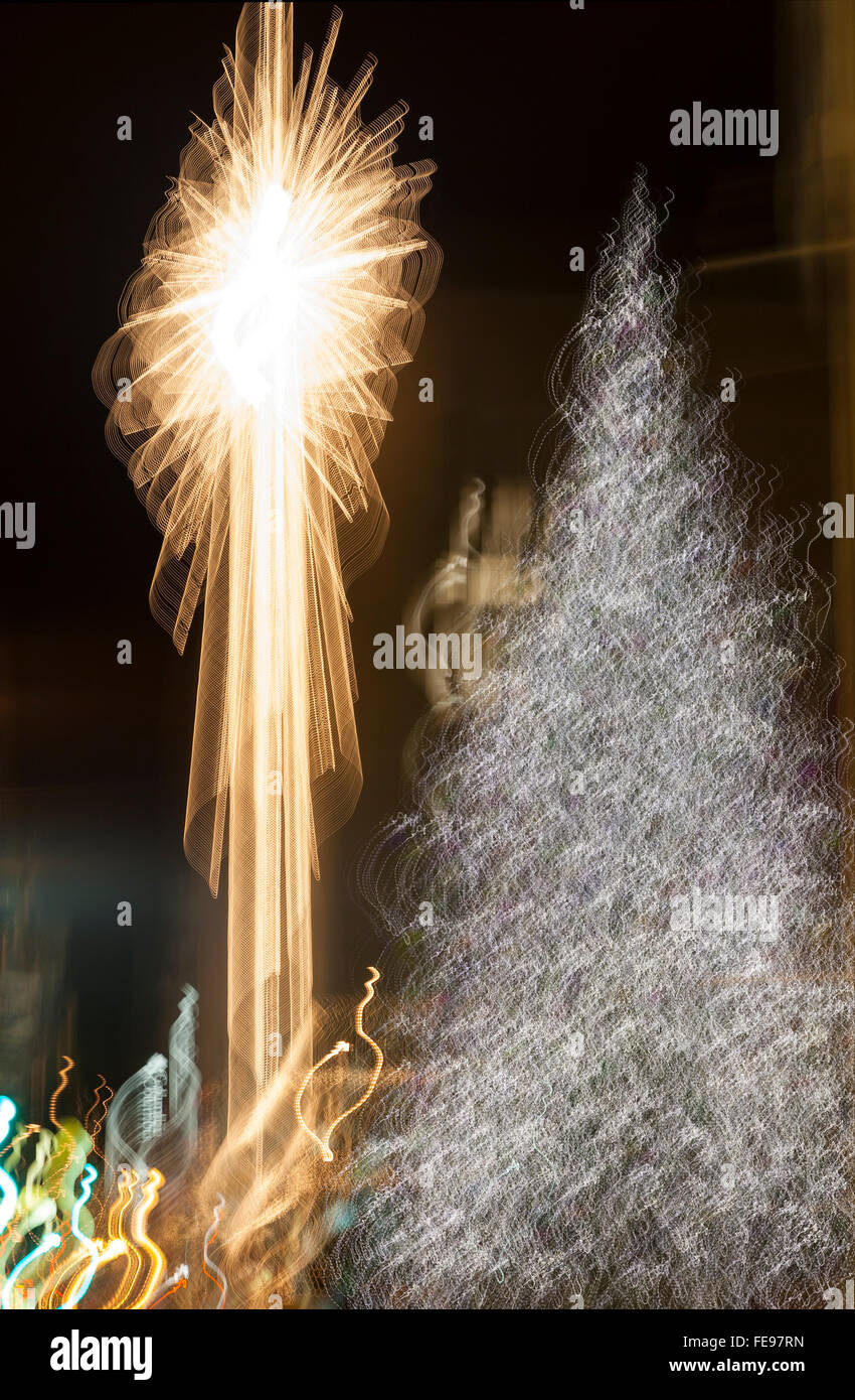 Abstract Christmas tree and lights in city at night. Bright holiday decorations background. - Stock Image