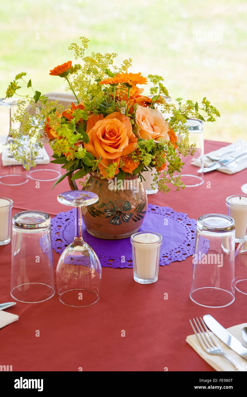 Casual table setting with glassware and bouquet of flowers at ...