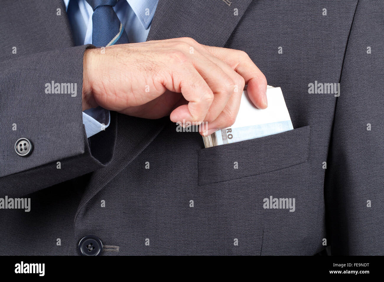 Businessman in suit putting a wad of money in his pocket. - Stock Image