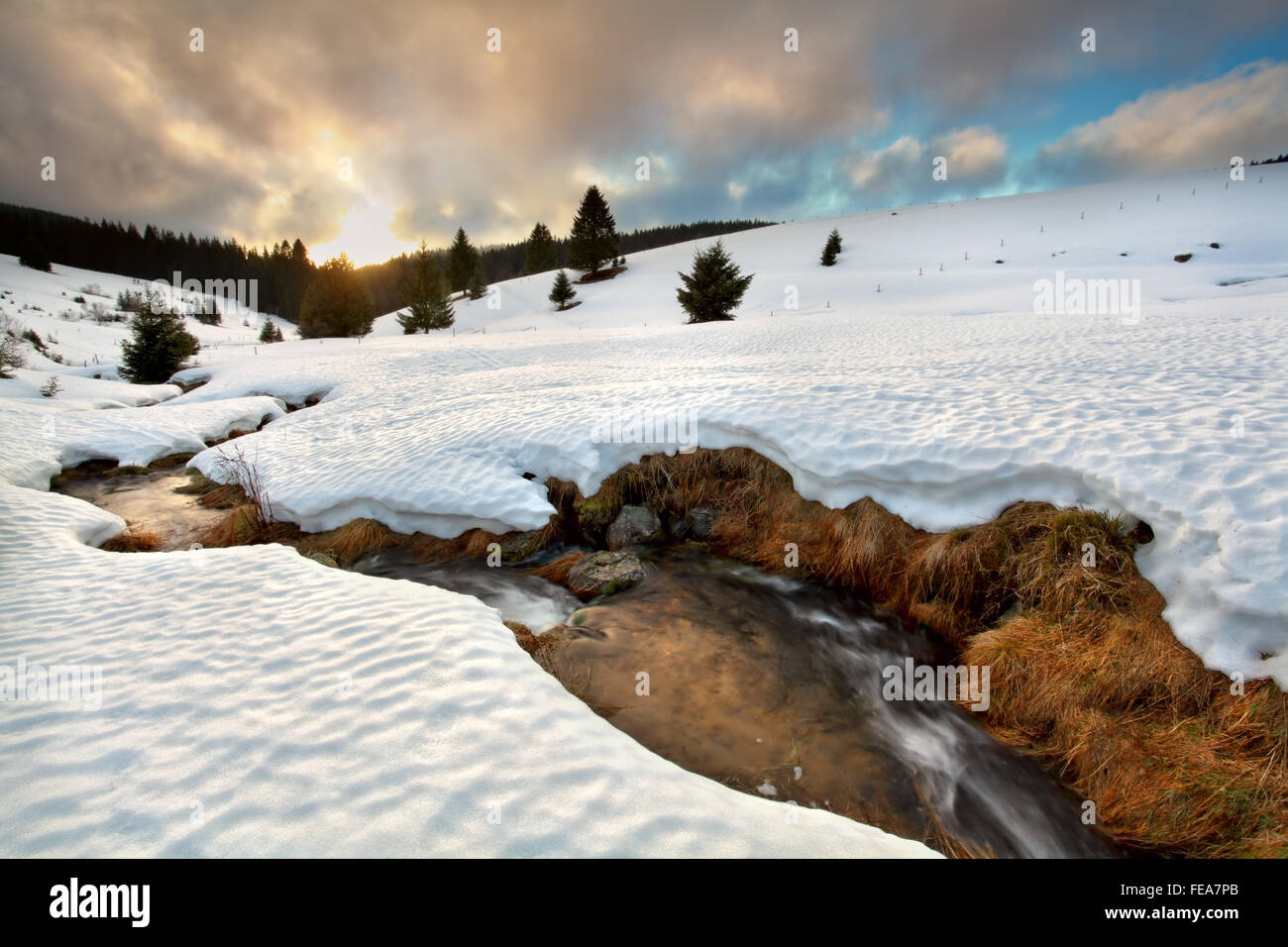 gold sunset over mountain river in winter, Todtnauberg, Waden-Wurttemberg, Germany - Stock Image