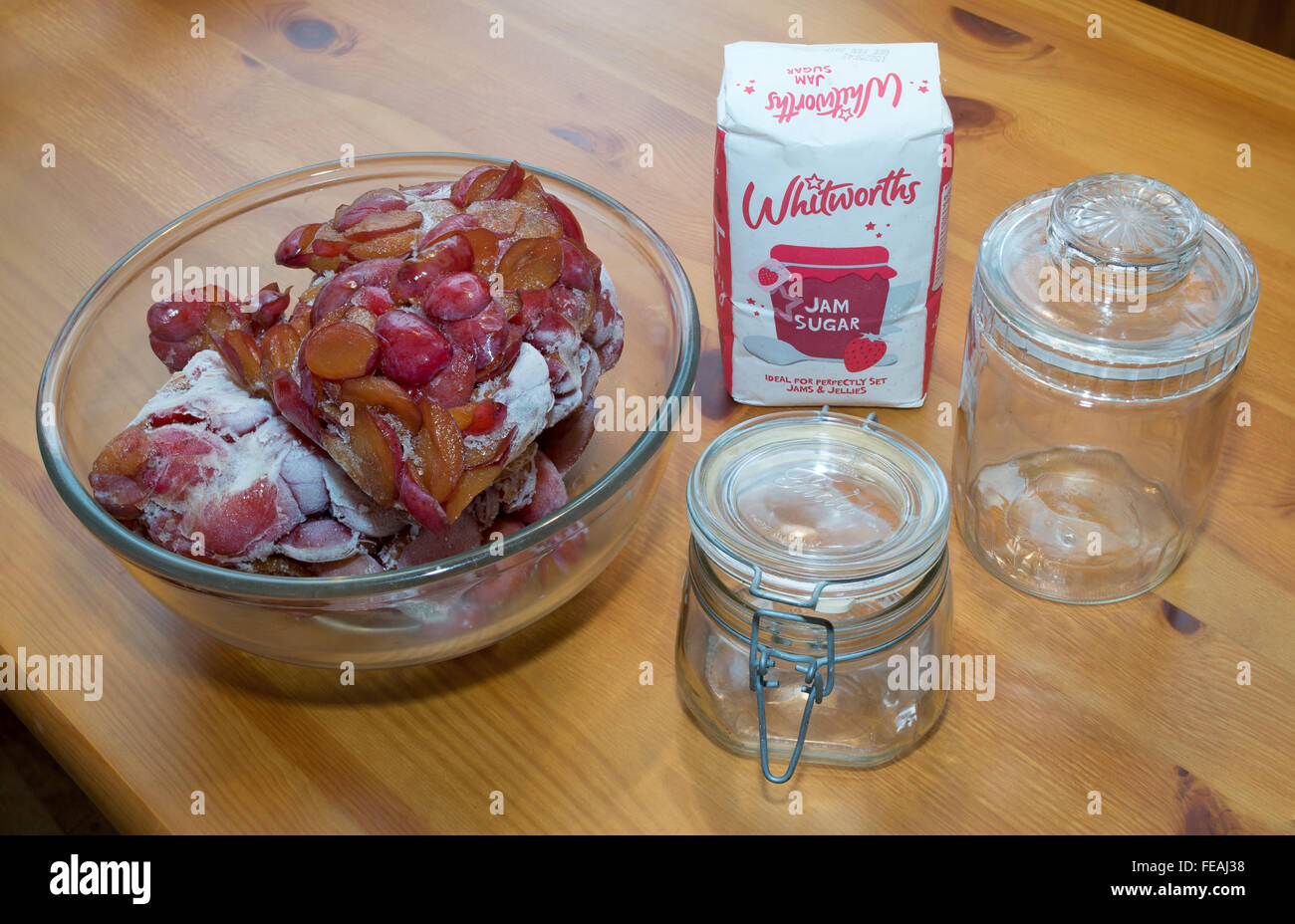 Plum jam making ingredients, defrosting plums, Whitworths jam sugar and preserving jars. - Stock Image