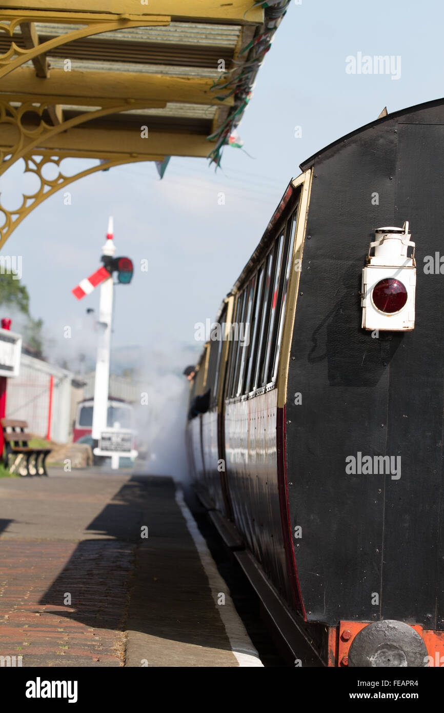 Bala Departure, in bright sunshine a train leaves the station on the Bala Lake Railway, focus on the tail lamp at - Stock Image