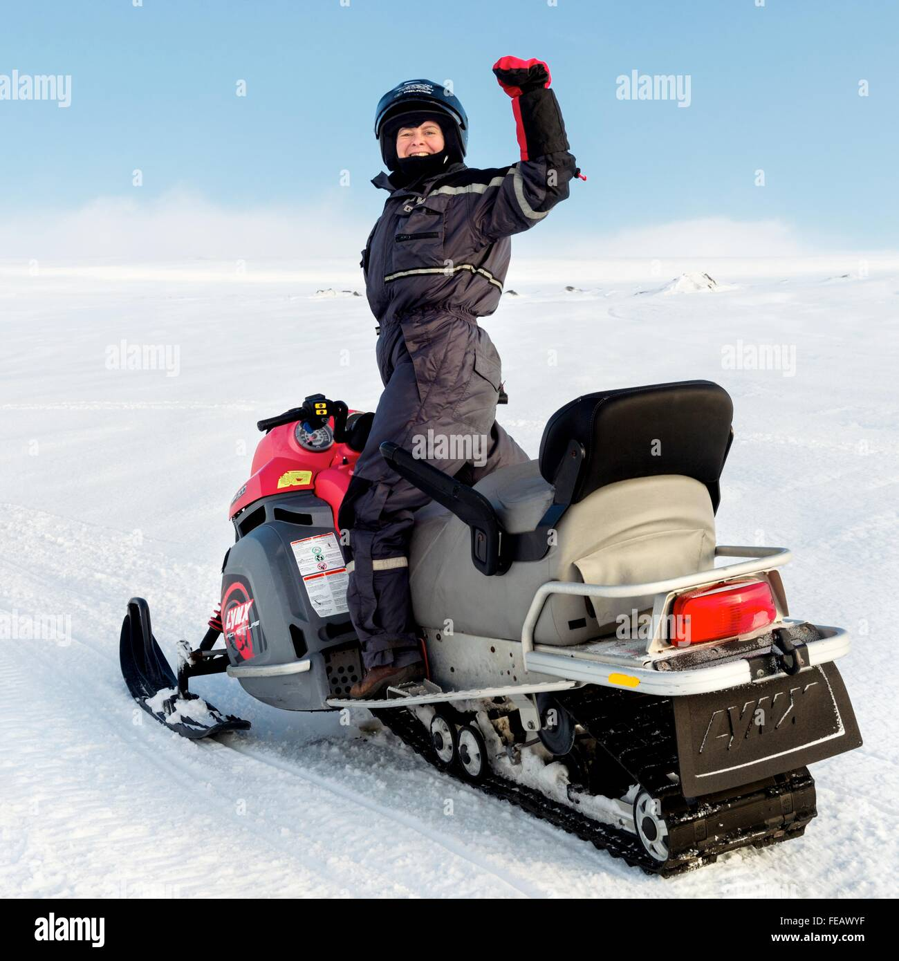 Woman on snowmobile on glacier in Iceland. - Stock Image