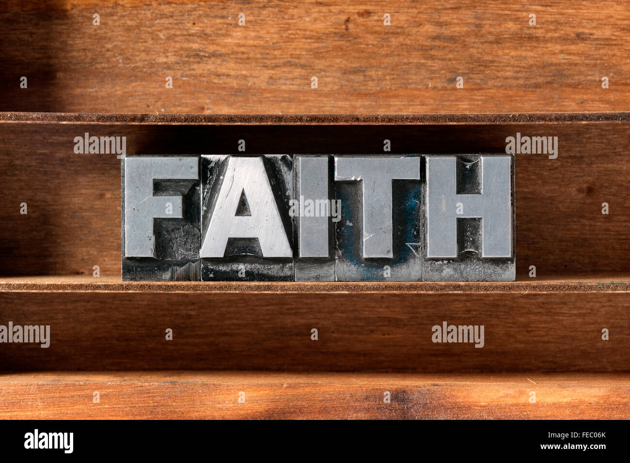 faith word made from metallic letterpress type on wooden tray - Stock Image