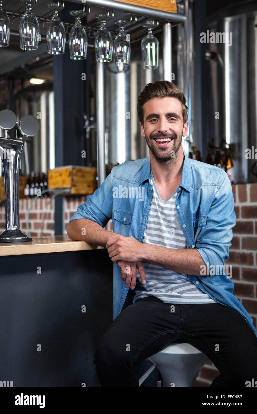 Handsome man leaning his elbow on the counter - Stock Image