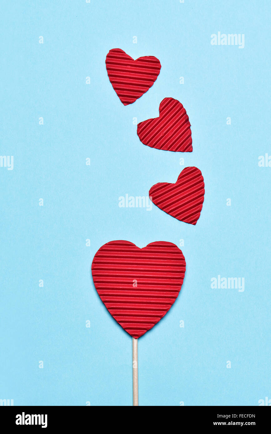 some hearts made with red corrugated paperboard, one of them stacked in a stick like a lollipop, against a blue - Stock Image