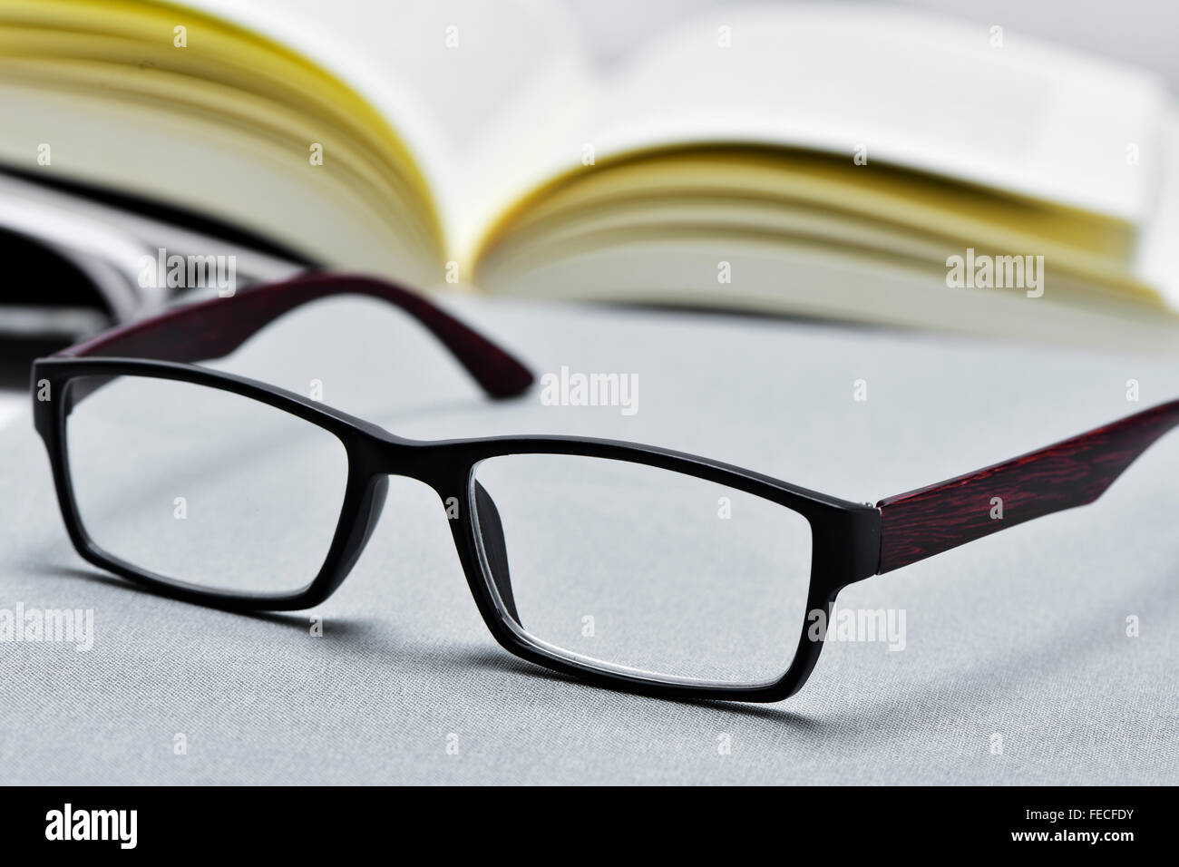 closeup of a pair of eyeglasses and an open book in the background - Stock Image