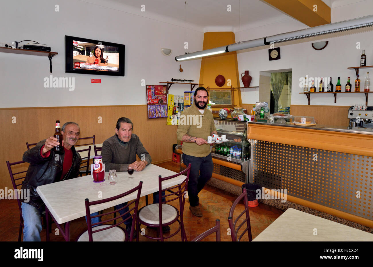 Portugal, Alentejo: Bar owner Sérgio serving coffee with clients having a drink in the Retired´s Club - Stock Image