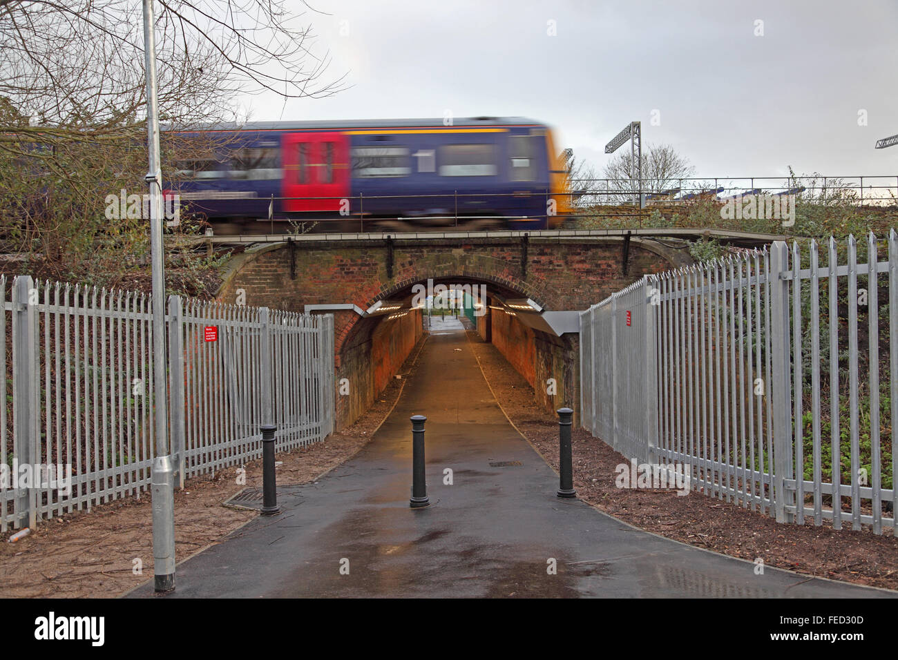 An old tunnel converted to a footpath/cycleway newly opened and brightly lit with a speeding train passing over - Stock Image