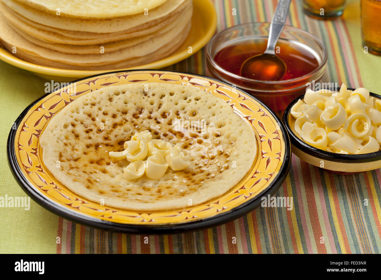 Traditional Moroccan beghrir pancakes with butter and honey - Stock Image