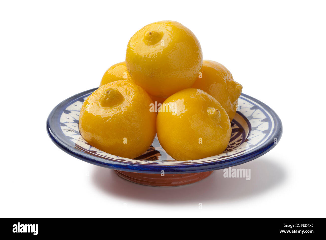 Bowl with Moroccan preserved lemons on white background - Stock Image