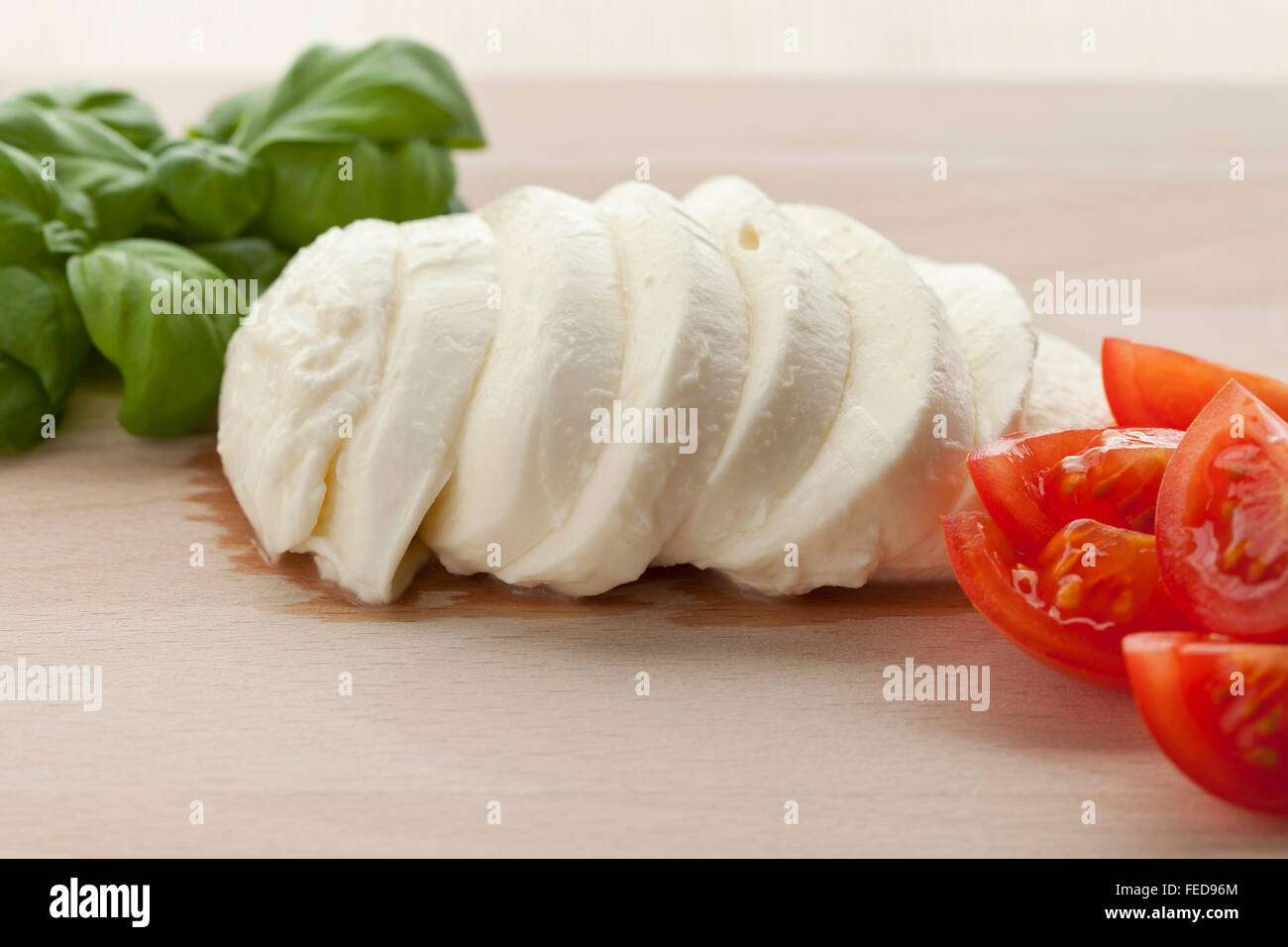 Fresh Mozzarella slices with basil leaves and tomatoes on wooden board - Stock Image