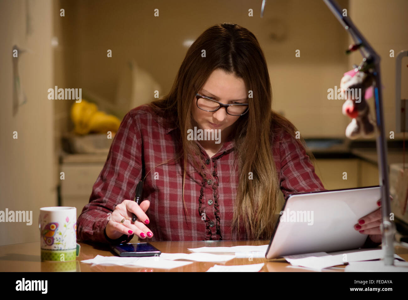 Young housewife paying bills online late in the evening after finishing all her house work, sitting at the desk - Stock Image
