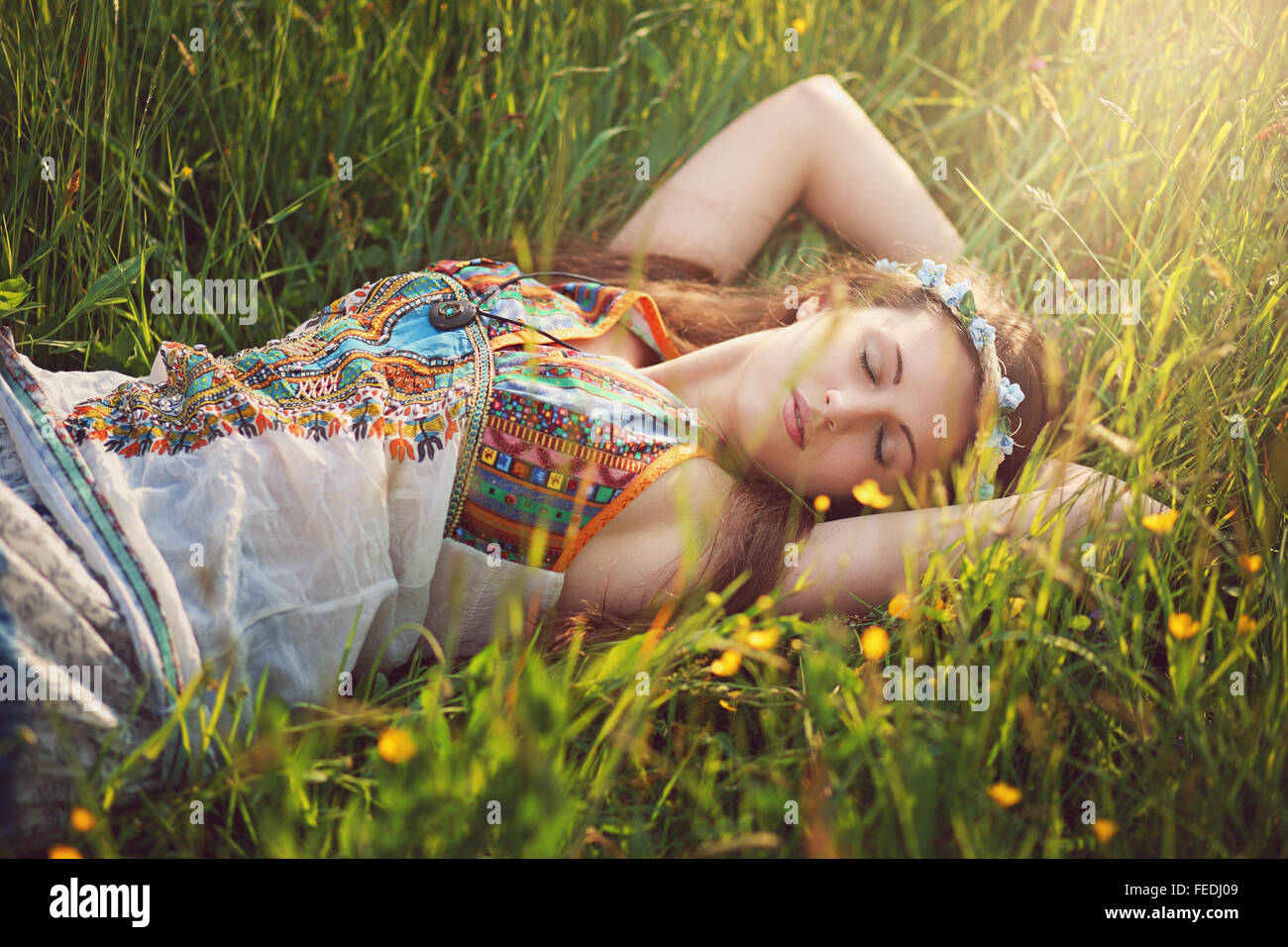 Beautiful hippie woman peacefully sleep in spring meadow - Stock Image