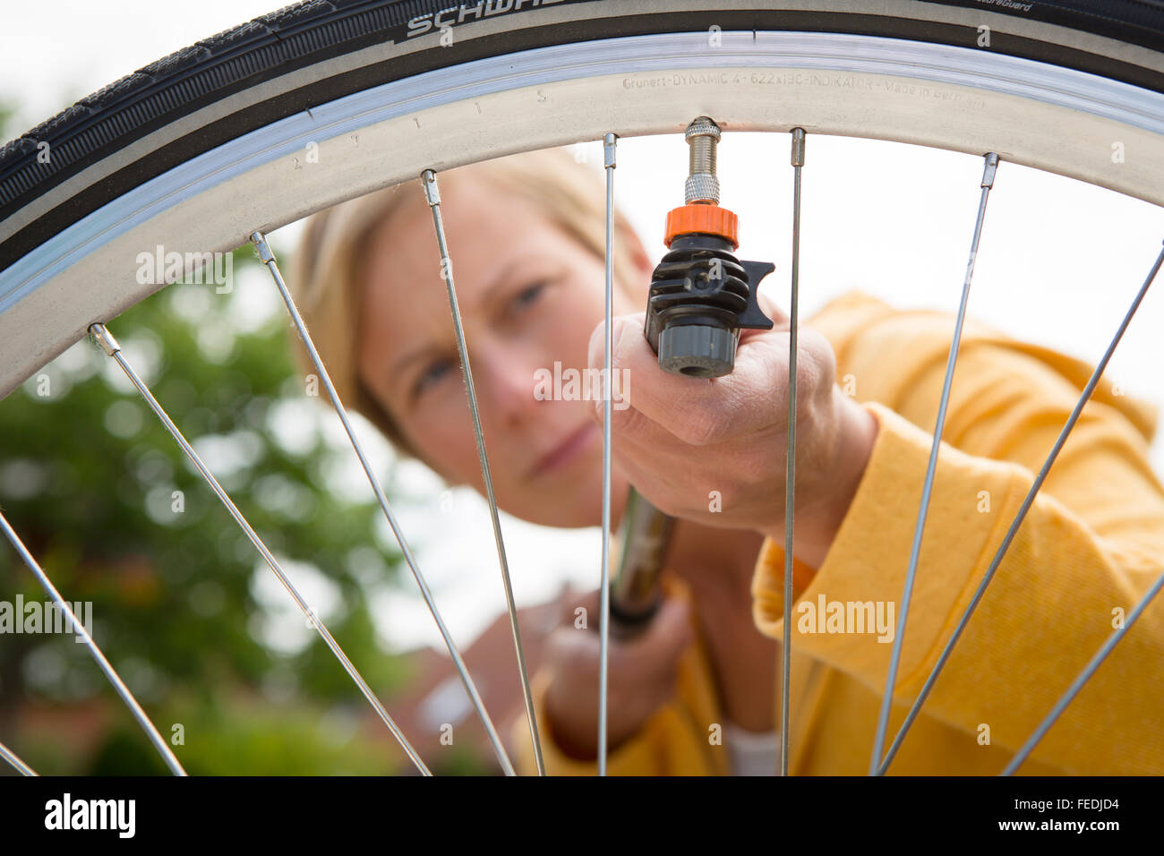 Woman pumps the tires on her bicycle wheel - Stock Image
